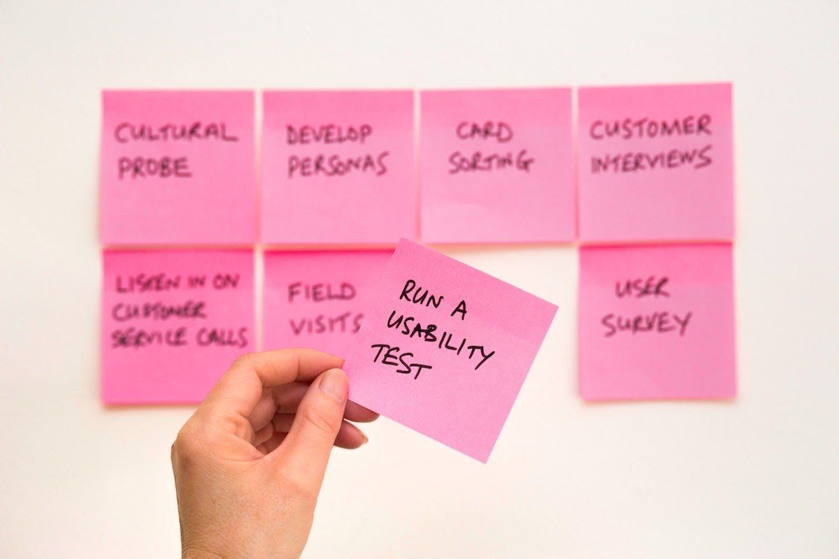 hand putting pink sticky note on wall best online business to start