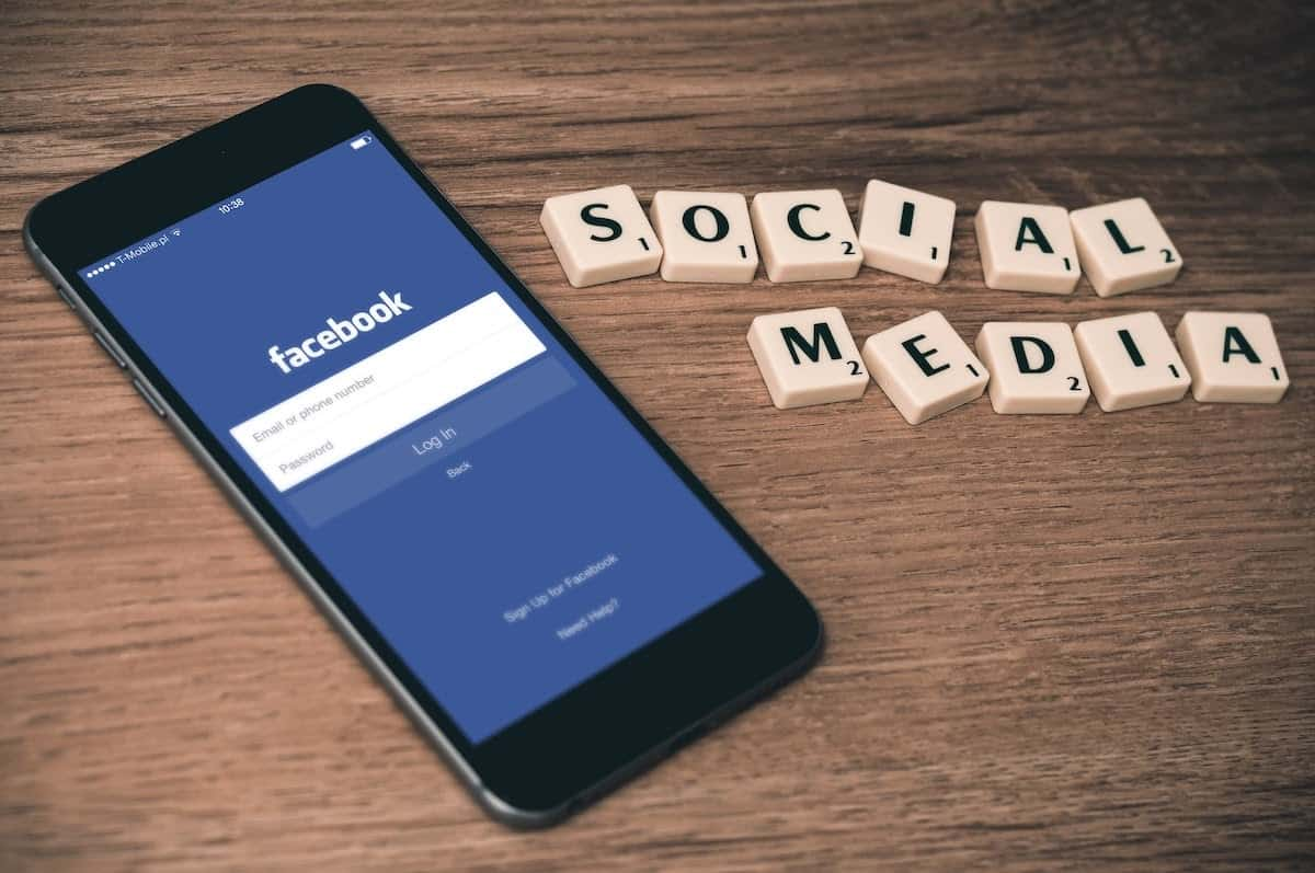 phone with facebook login and scrabble letters saying social media