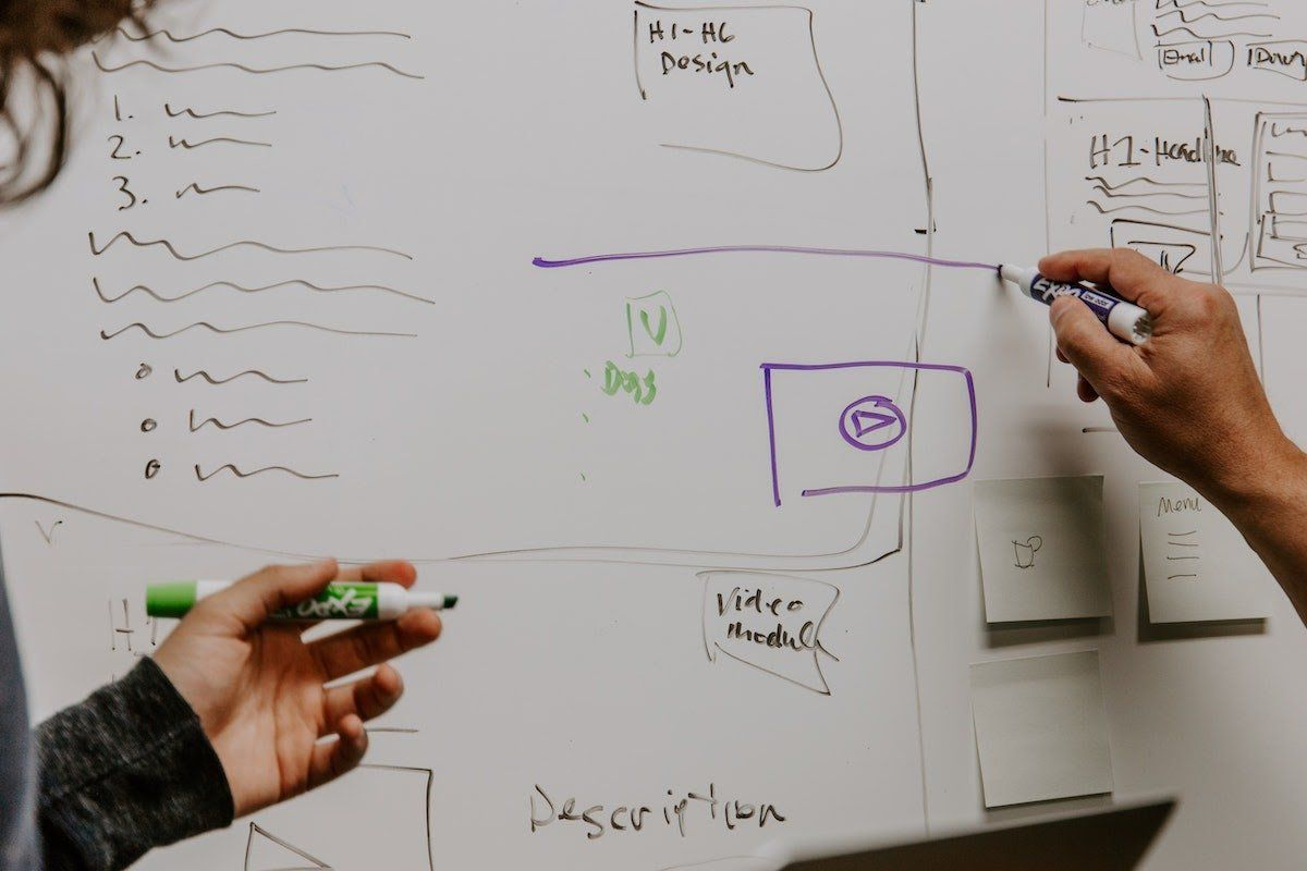two people at whiteboard <span class='ent _drawing'>drawing</span> plans