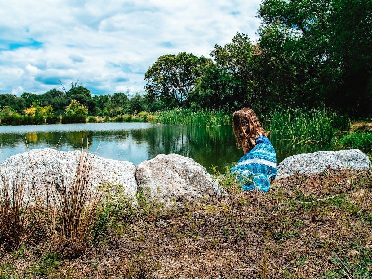 woman sitting at edge of pond